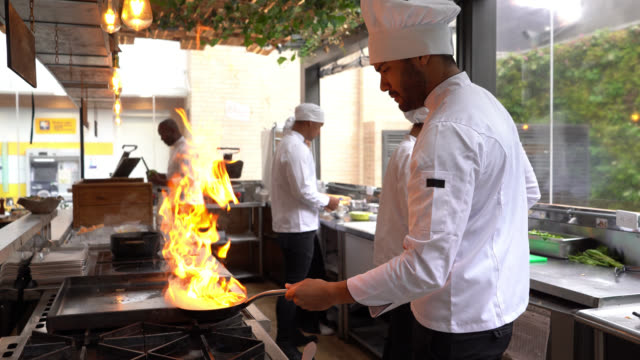 chef cooking flambe in a pan looking focused - chef stock videos & royalty-free footage