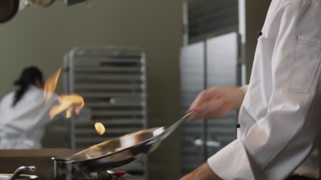 vídeos y material grabado en eventos de stock de ms tu td chef cooking in kitchen / orem, utah, usa - sartén