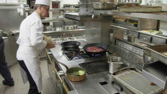 POV chef cooking meat in pans on gas-fired hob (range) in a restaurant kitchen