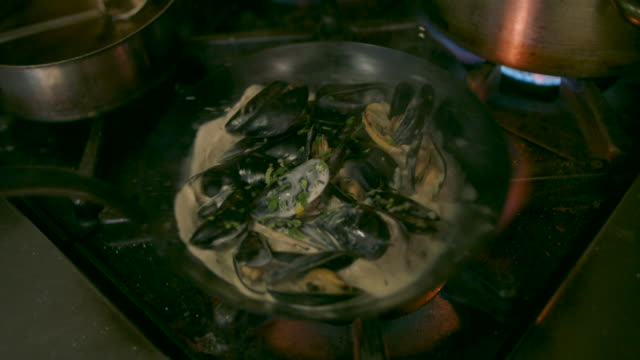 chef cooking mussels in pan - kingsand video stock e b–roll