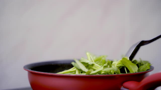 vidéos et rushes de chef cuisson remuer les épinards à l'eau frite dans une casserole chaude. - plat végétarien