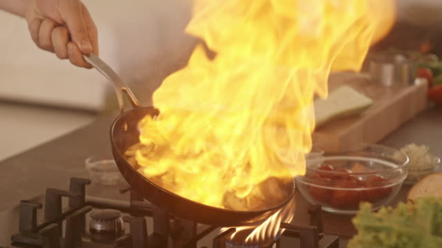 chef cooking with fire, grilling vegetables - mixing stock videos and b-roll footage