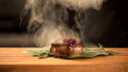 chef cooks food in the kitchen. Fry steak meat. final serving dish. slow motion