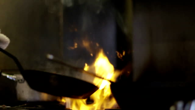 chef cooks with a pan over a fire - cu, slow motion - chef stock videos & royalty-free footage