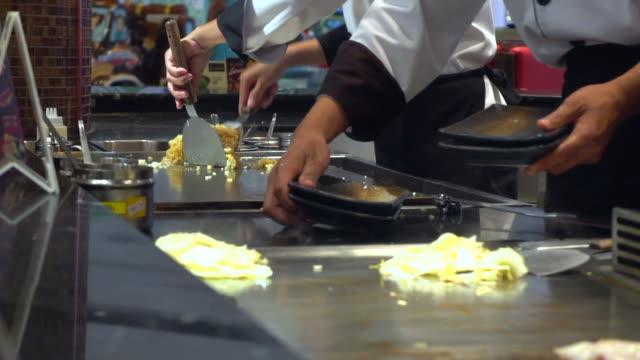 chef kocht mit einer pfanne über dem feuer - skillet cooking pan stock-videos und b-roll-filmmaterial