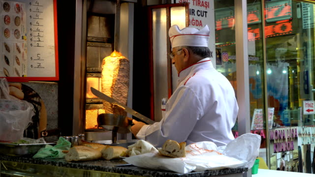 chef cuts doner kebab which is the most popular fast food in turkey. man with a knife cut meat for shawarma or denner on a special skewer - middle east stock videos & royalty-free footage
