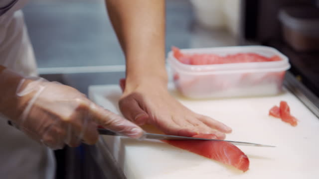 CU A chef cuts fish in a sushi restaurant / Tokyo, Japan
