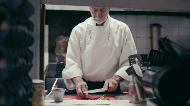 vídeos y material grabado en eventos de stock de chef cortando el ajo en una cocina de restaurante italiano - chef