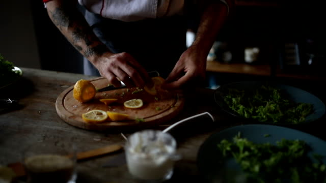Chef cutting lemon for decoration on plate