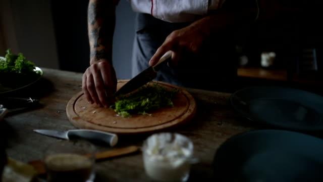 vidéos et rushes de chef couper la laitue en tranches - tatouage
