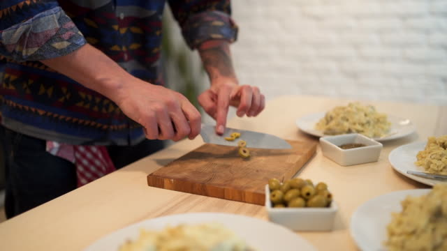 Chef cutting olives for meal decoration