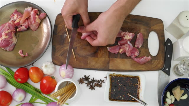 A chef cutting pieces of chicken on a wooden cutting board on a white kitchen table top with ingredients for preparing chicken satay
