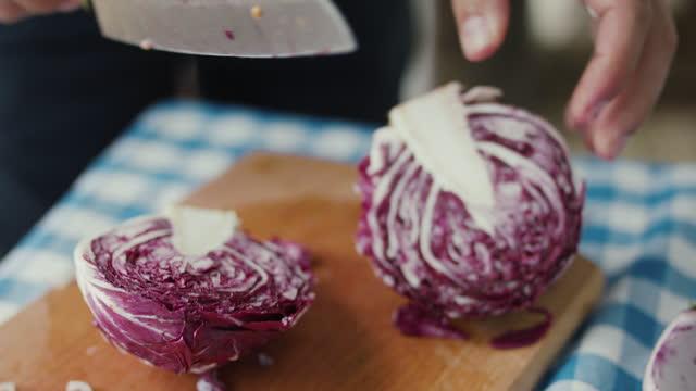 chef cutting radicchio in half - freshness stock-videos und b-roll-filmmaterial