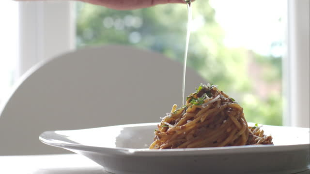 Chef dressing pasta with olive oil