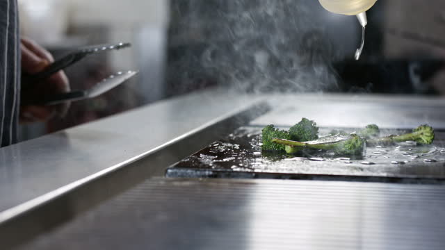 chef drizzling oil on broccoli on hot plate - crucifers stock videos & royalty-free footage
