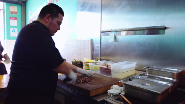 chef expertly chopping meat in taqueria kitchen - commercial kitchen stock videos & royalty-free footage
