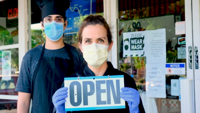 chef fast food restaurant and mature female owner posing wearing a mask holding an open sign - state of emergency stock videos & royalty-free footage