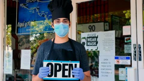 chef fast-food-restaurant-besitzer posiert mit einer maske mit einem open sign - arbeitslosigkeit stock-videos und b-roll-filmmaterial
