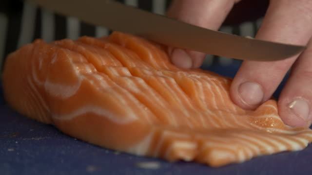 Chef filleting salmon and slicing fillet with knife