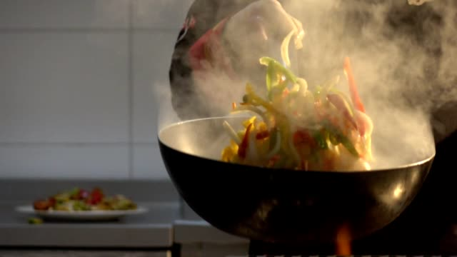 stockvideo's en b-roll-footage met chef-kok flambaying groenten - pannen