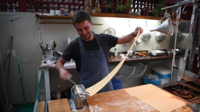 vídeos de stock, filmes e b-roll de chef de achatamento mão fresca fiz macarrão na máquina - massa alimento básico