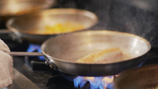 Chef flips fish in flaming skillet and shakes corn over gas stove top in restaurant kitchen