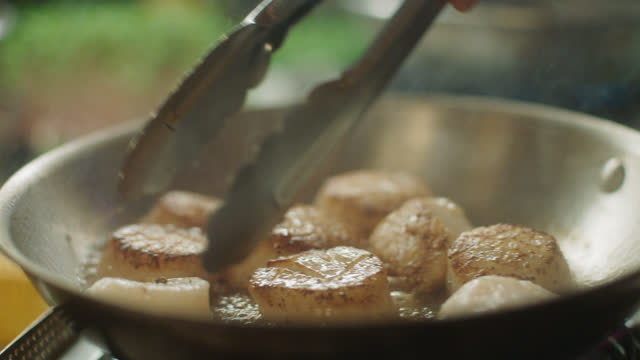 slo mo cu chef flips half-cooked scallops over in a skillet - フライパン点の映像素材/bロール