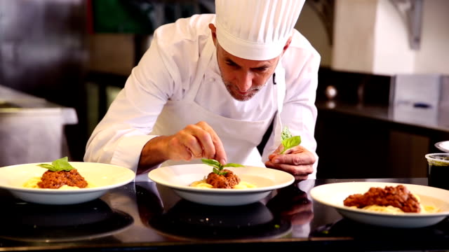 Chef garnishing pasta dish with basil leaf