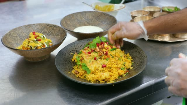 chef giving final touch with garnish to a freshly cooked biryani - vassoio video stock e b–roll