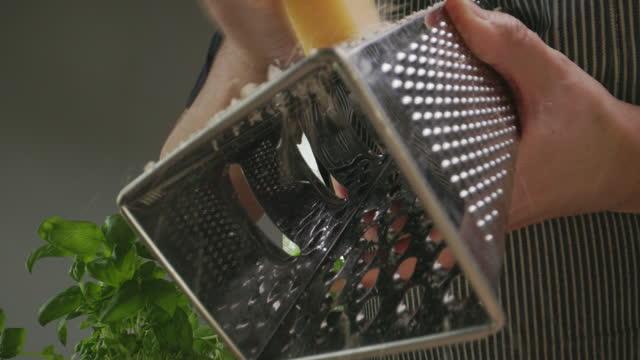 vídeos y material grabado en eventos de stock de chef ralla queso en plato de pasta fresca - part of a series