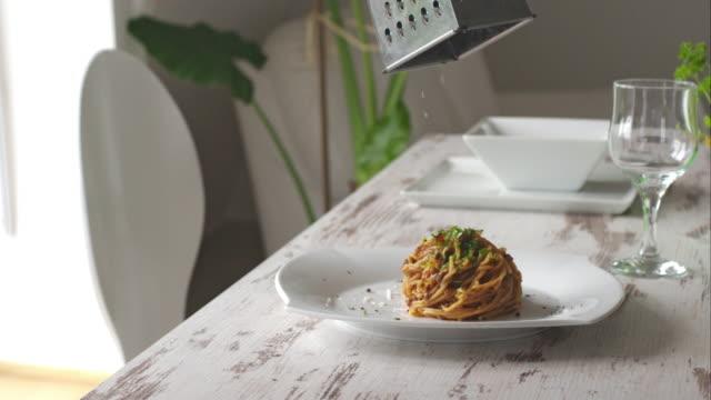 Chef grating parmesan cheese on vegetarian pasta
