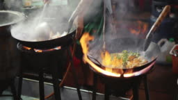 Chef hand cooking with fire pan, street food