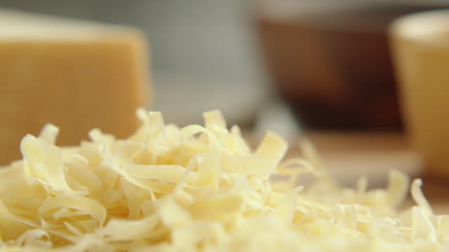 ecu r /f chef hand picks up coarse cheese gratings and sprinkles them back into pile / los angeles, california united states - cheese stock videos & royalty-free footage