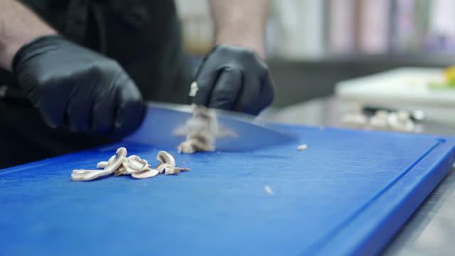 stockvideo's en b-roll-footage met de handen die van de chef-kok eetbare paddestoel bij commerciële keuken snijden - paddenstoel