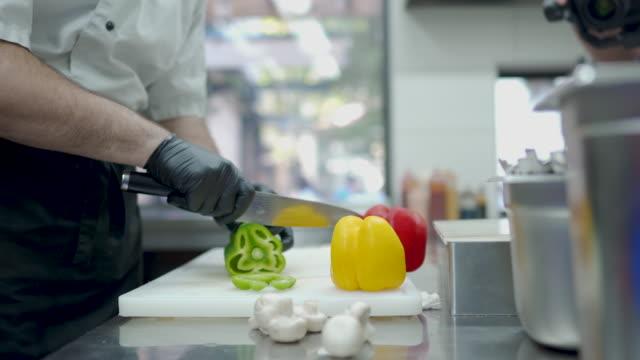 chef hände schneiden pfeffer in der kommerziellen küche - scharfe schoten stock-videos und b-roll-filmmaterial