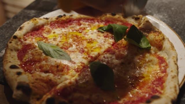 シェフの手は、ピザのかわいいで焼きたてのピザをカット - 焼いた点の映像素材/bロール