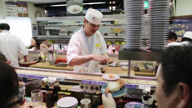 vídeos de stock e filmes b-roll de ws a chef hands sushi to customers in a tokyo restaurant / tokyo, japan - sushi