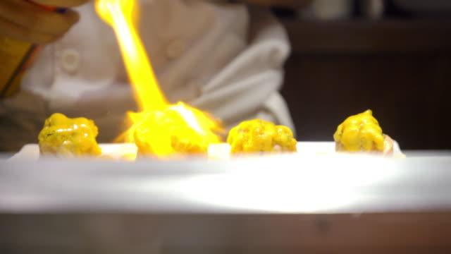 レストランのキッチンでキッチンブローチを持ち、日本料理の表面に燃えるシェフ - ガス台点の映像素材/bロール
