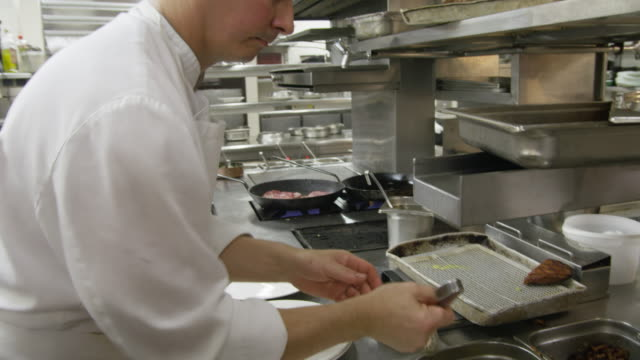 POV LA chef in restaurant kitchen placing potatoes on plates in preparation for plating