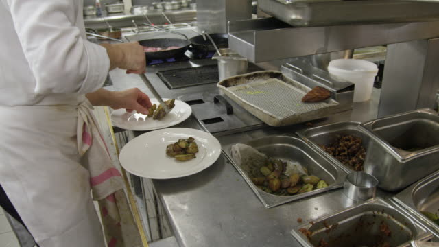POV HA chef in restaurant kitchen placing potatoes on plates in preparation for plating