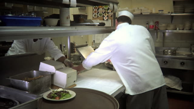 ms chef in restaurant's kitchen wiping off plate edges before placing them onto tray / windsor, vermont, usa - dishcloth stock videos & royalty-free footage