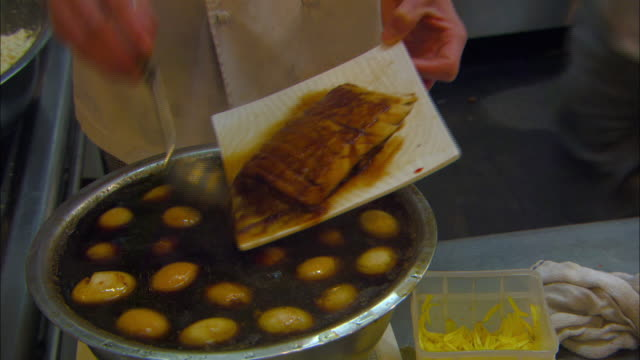 a chef ladles sauce over a fish fillet in a restaurant kitchen. - sauce stock videos and b-roll footage