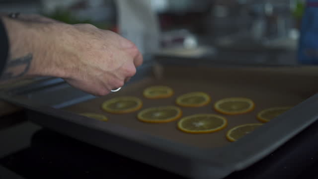 chef laying out sliced oranges in kitchen pan - one young man only stock-videos und b-roll-filmmaterial