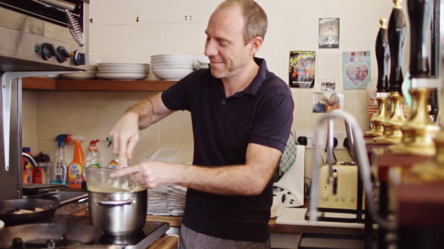 chef making hollandaise sauce in small cafe kitchen - hollandaise sauce stock videos and b-roll footage