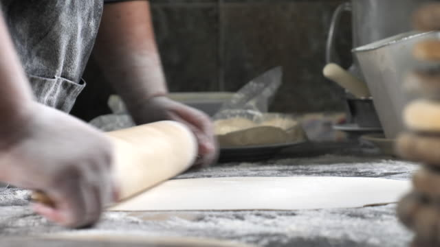 chef making pizza, rolls out the dough with a rolling pin - rolling pin stock videos & royalty-free footage