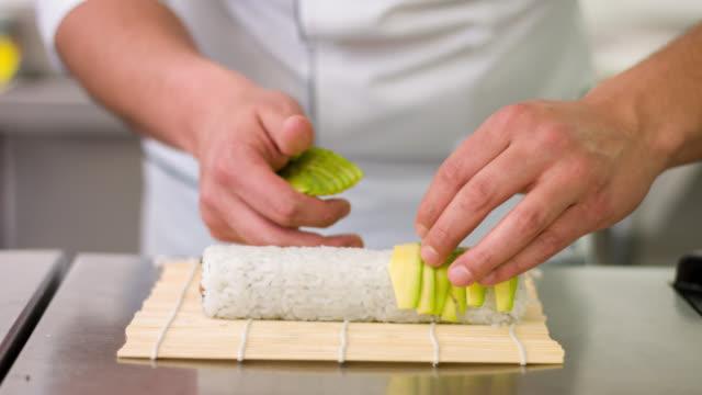 vídeos y material grabado en eventos de stock de hacer sushi chef - aguacate