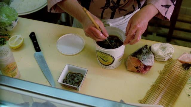 vídeos de stock, filmes e b-roll de ms pan chef making various sushi item - estampa de folha