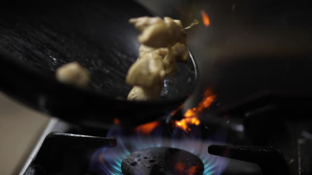 chef mixing chopped chicken breast in frying pan at commercial kitchen - natural gas stock videos & royalty-free footage