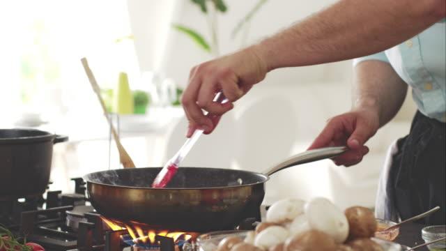 chefkoch aus fleisch und andere zutaten im bratpfanne - skillet cooking pan stock-videos und b-roll-filmmaterial