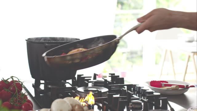vidéos et rushes de le chef préparer les pâtes à la sauce tomate à gaz d'une cuisinière - secouer